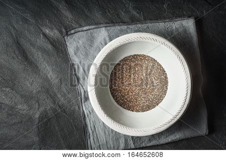 Chia seeds in the white plate on the dark stone table top view