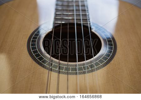 wooden guitar strings closeup, stringed musical instrument