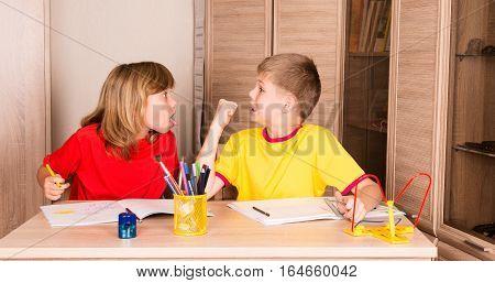 Children quarreling. Sister teasing brother while doing homework together.