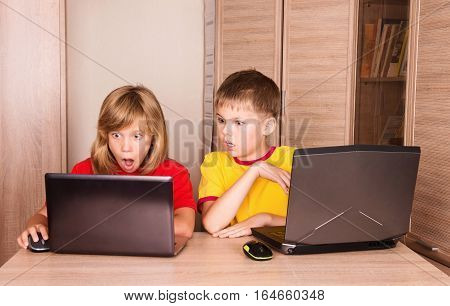 Computer problems. Stressed frustrated and scared children having computer problems. Cute girl and boy using laptops at home.