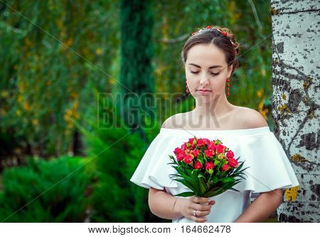 Portrait of beautiful young bride in white frilly dress with open shoulders and red earrings looking at wedding bouquet of small red roses in her hand, standing in the autumn park