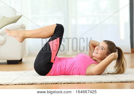 Side view of a fitness girl doing crunches lying on the floor in the living room at home and looking at you