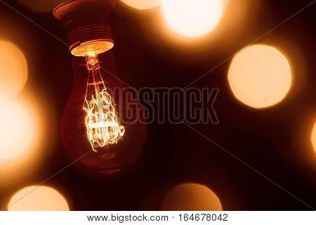 lighted vintage incandescent bulb on dark orange blurred background