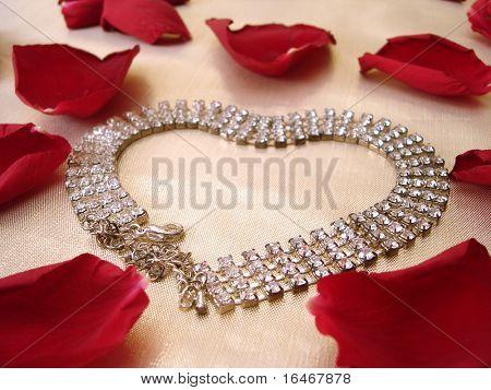 heart of dimond necklace with red rose petals on golden