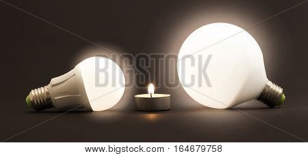 White little candle and LED electric bulbs on dark background. Concept describing the evolution of lighting and energy saving.