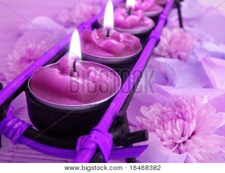 row of violet candles over straw matt with rose petals