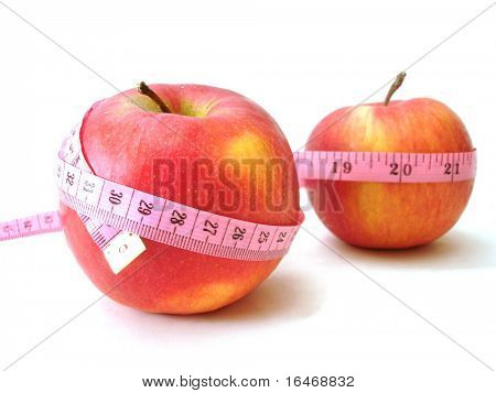 apples with pink tape measure over white background (concept of health, diet)