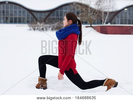 Young brunette woman performing a front lunge on a snowy field outdoors