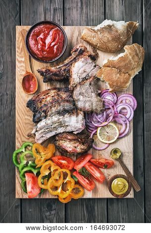 Sliced grilled pork with vegetables on wooden board top view. Flat lay style