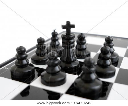 Black chess king stands on a chess board with figures