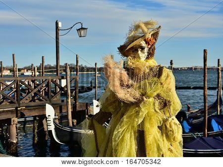 VENICE, ITALY - FEBRAURY 4: Carnival of Venice beautiful mask with gondola and lagoon FEBRUARY 4, 2016 in Venice, Italy