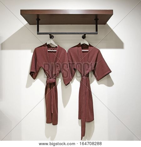 two off brown bathrobes hanging on rack