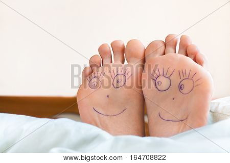Healthy female feet with smiling faces on it. Joy, health.