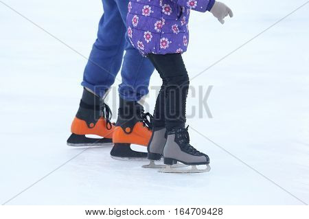 the legs of a man and girl skating on an ice rink.