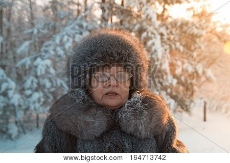 Portrait of senior woman fur coat and hat standing in cold winter snow covered forest, close up