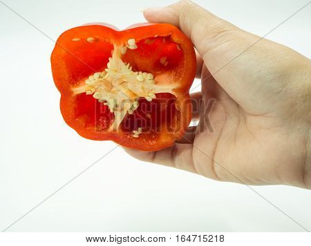 Human's hand holding half of paprika on white background sweet pepper bell pepper