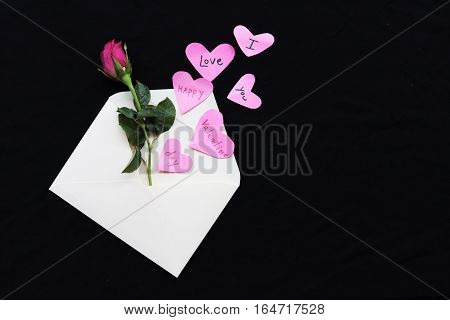 happy valentine day i love you words message on heart and rose out of envelope on background black