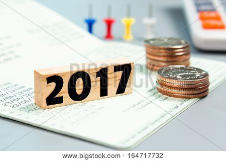 Text message 2017 on wooden with book bank, stacked coins. Finance concept