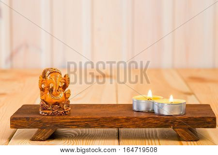 Wooden Statuette Of The God Ganesha And A Candle On A Support