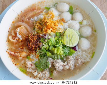Rice porridge with shrimp, fish ball, pork, crispy squid, coriander, spring onion, pepper powder, chili powder, lime