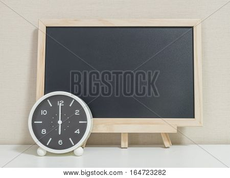 Closeup alarm clock for decorate show 6 o'clock with wood black board on white wood desk and cream wallpaper textured background selective focus at the clock
