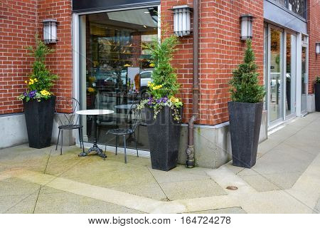 Street caffe for two at the shop window. Flowerbeds marble table and two chairs as a small caffe outside