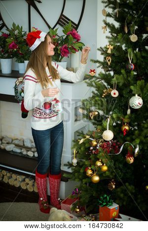 Side view of attractive young smiling brunette in red cap decorates christmas tree