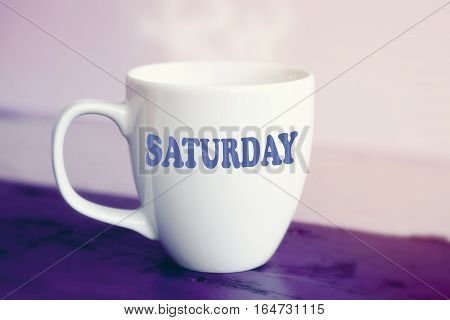white cup with the word Saturday on it on purple wooden table