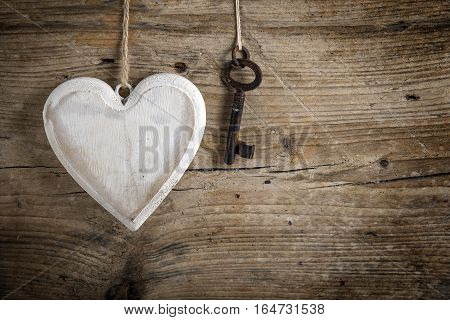 Heart from white painted wood and an old key hanging on a rustic wooden wall love concept for valentine's or mother's day with copy space