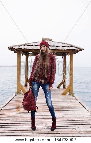 young beautiful woman in a burgundy jacket posing on a background of a wooden pavilion at the pier near the sea