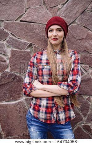 portrait of beautiful young woman in burgundy hat and plaid shirt on the background of a stone wall