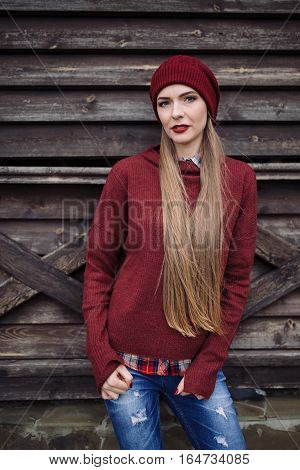 portrait of beautiful young woman in burgundy hat and sweater on a wooden background