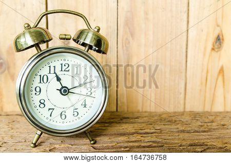 Old vintage alarm clock with bells on old wooden background