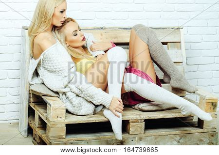 Pretty girls or two sexy cute women with blond hair in home sweaters and socks sit on wooden pallet sofa on white brick wall
