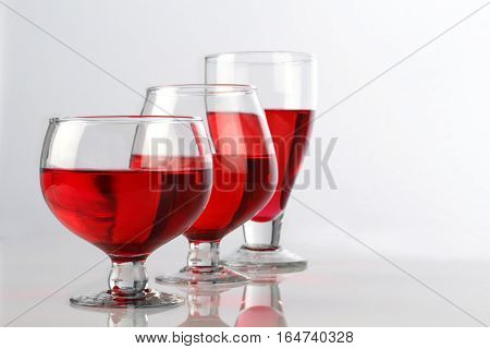 Red Wine Glasses on White Reflective Background
