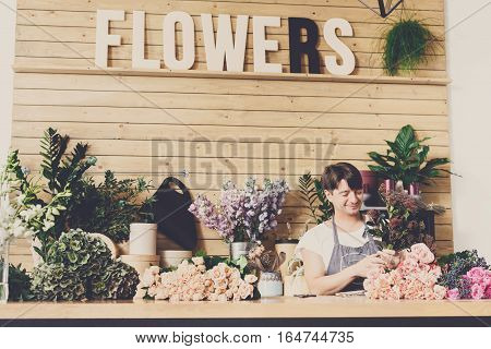Small business, flower shop. Male florist making bouquet. Man assistant or owner in floral design studio, making decorations and arrangements. Flowers delivery, creating order. Filtered
