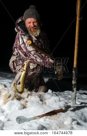 Bearded man is holding fish and smiling at dark winter night after fishing