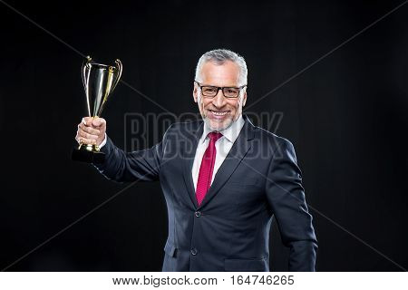 Happy mature businessman holding award cup on black
