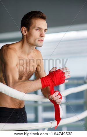 Athletic man close up near boxing ring with boxing bandages