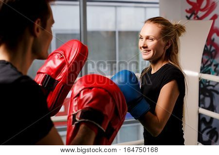 Exercise young sportswoman with trainer in boxing gloves in gym