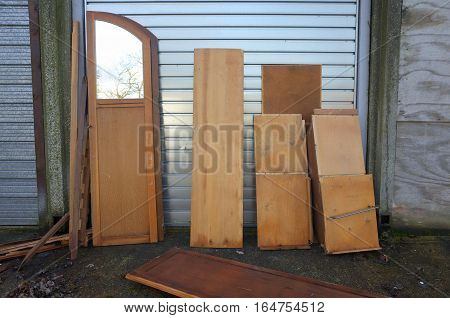 Dismantled and discarded wooden wardrobe or cabinet dumped in front of a garage or storage space