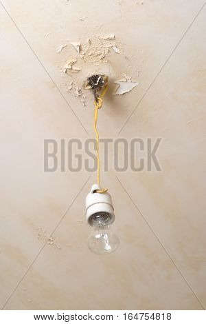 Electric bulb hanging from ceiling in bad condition