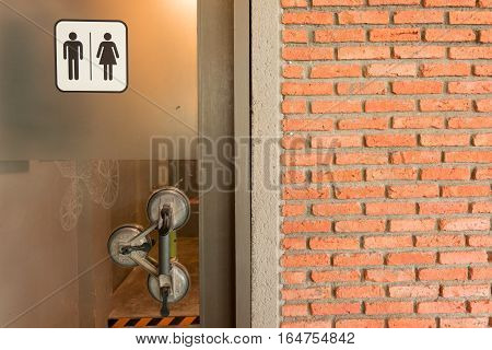 Brick wall background with toilet signs on door glass