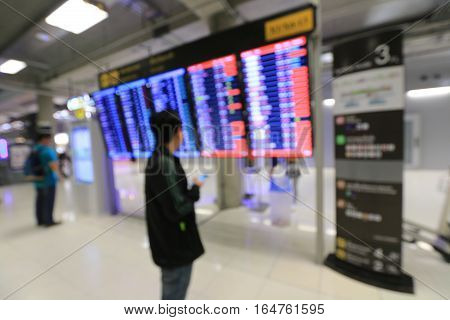 Blur Image Of Blue Screen Flight Schedules And People Seeing And Waiting For Person In Airport For B