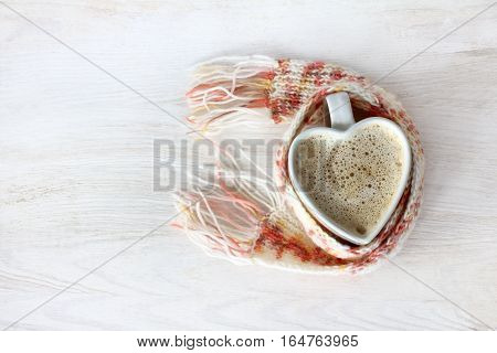 heart symbol in the form of a cup of coffee with foam wrapped in a warming scarf / aspiration good feelings