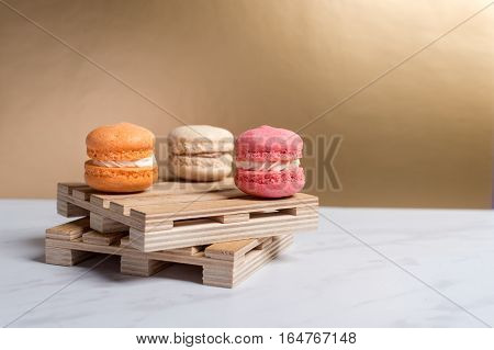 Sweet and colourful macaroons served on little wooden pallets on a marble texture table and golden background. Traditional french dessert. Copy space