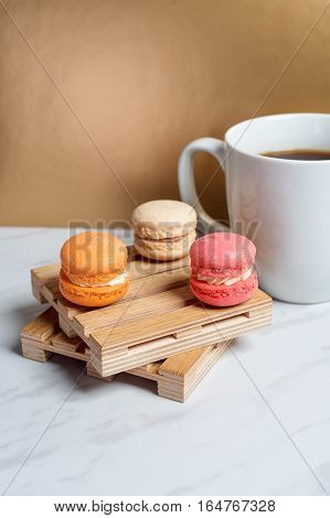 Sweet and colourful macaroons served on little wooden pallets with cup of coffee on a marble texture table and golden background. Traditional french dessert. Copy space