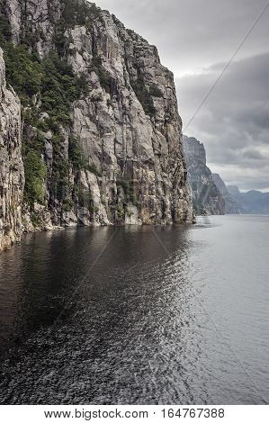 Norway Lysefjord. Rocky coast fjord teeming with cracks and waterfalls. Cloudy rainy day.
