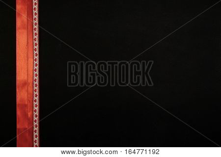 Copy space on black with red ribbons