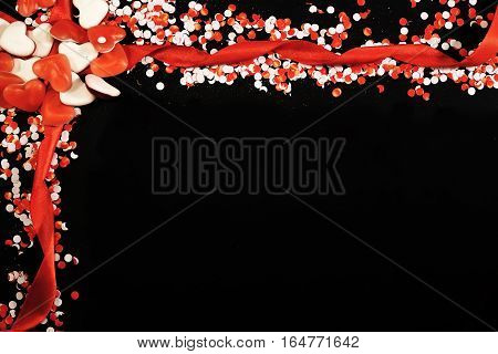 White and red confetti and candies on blackboard